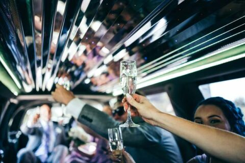 People holding their glass of wine in the limo